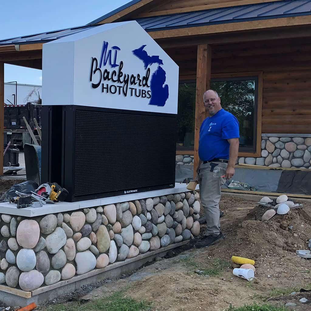 John Jones in front of Mi Backyard Hot Tubs Sign